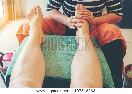 Asian woman having traditional Thai foot massage