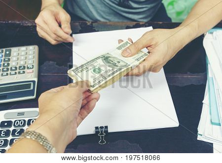 Business concept : hand paying U.S dollar bills trading for merchandise