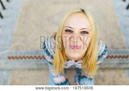 Blonde girl portrait grimacing. Smiling young woman with piercing on her lips looking up at camera and sitting on concrete steps. Happiness and carefree concepts