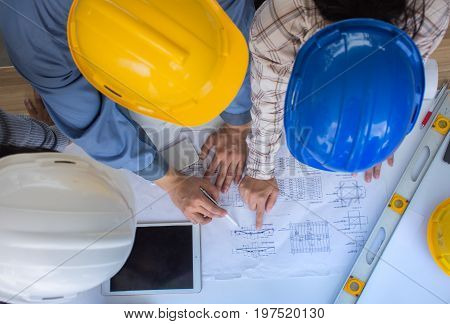 Engineering team is meeting, planning construction work, Engineer team looking paper plans at construction site,overhead view, Top view Concept for team work