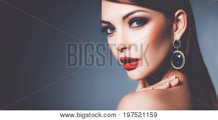 Portrait of beautiful young brunette woman in ear-rings .