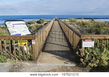 Waitpinga South Australia Australia: June 10 2017: Male photographer heading on to the beach and walking across the wooden foot bridge taking him from the car park to the beach beyond.