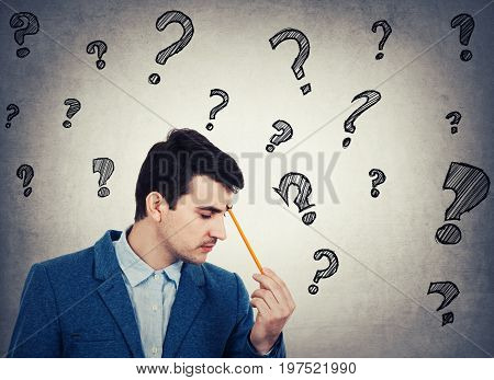 Thoughtful businessman holding a pencil pointed to face drawing different interrogation marks like questions escaping from head isolated gray wall background.