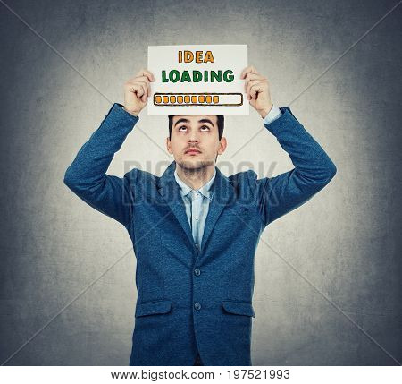 Businessman holding a white paper above head with a loading bar drawn symbolizing business idea load percentage isolated on grey wall background.
