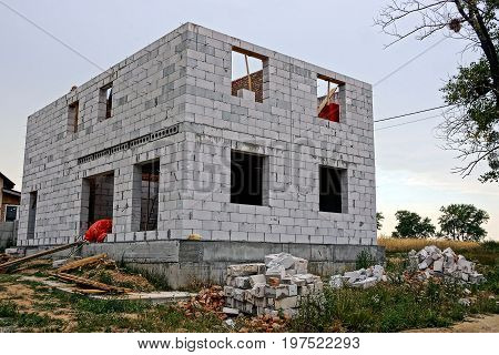 Construction site with unfinished house of white brick