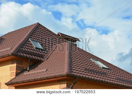 Roofing construction with attic skylights rain gutter system roof windows metal snow guard and guttering.