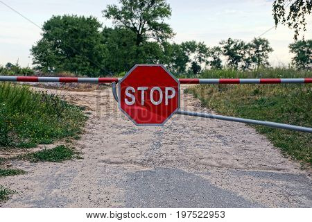 A barrier with a road sign blocks the road and prohibits the passage