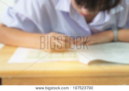 Blurred of Students using pencil writing information on white answer paper in high school Asian exams room Examination is assessment intended to measure knowledge skill aptitude Education Concept
