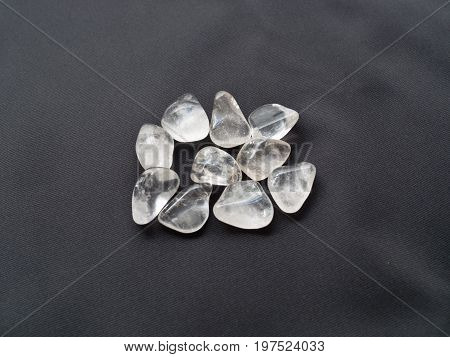 Tumbled Pink Quartz Stones Close Up On Black Cloth For Crystal Therapy Treatments And Reiki