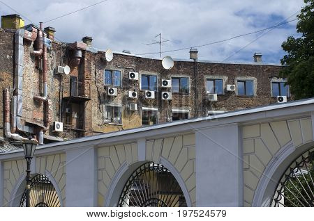 Old brick facade of the house with air conditioning and satellite antennas for arched fence