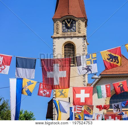 Wallisellen, Switzerland - 30 July, 2017: flags over Kirchstrasse street decorated for the upcoming Swiss National Day, selective focus on the foreground, the protestant church in the background. Wallisellen is a town in the Swiss canton of Zurich.