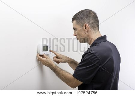 Hvac technician adjusting temperature on a digital thermostat