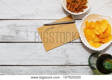 Vintage style post card on wooden table with bottle of light beer and different snacks - horizontal flat view