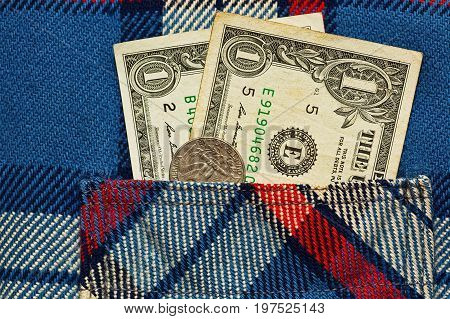 Just two american dollars and quarter in worker checkered shirt pocket - crisis symbol. Closeup macro capture