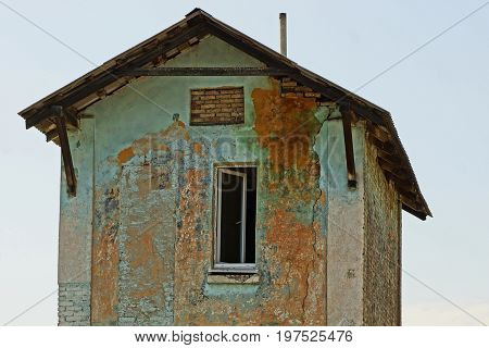 Facade of an old house with an open window on a sky background