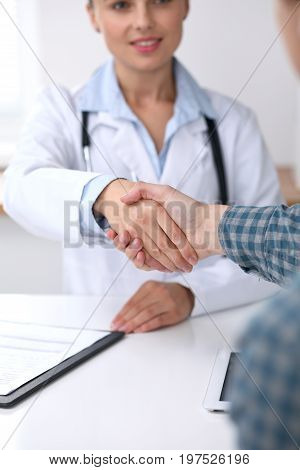 Close up of a doctor woman shaking hands with her male patient. Medicine and trust concept.