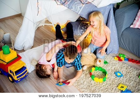 Three kids playing together in a wigwam in a living room