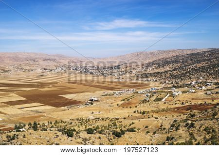 Orange fields between the mountains and blue sky in Beqaa Valley, Lebanon