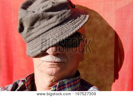 An Elderly Man Enjoys Relaxing On The Sun