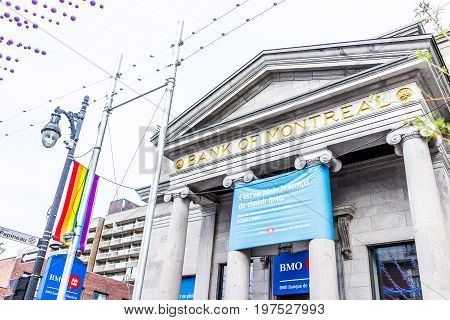 Montreal Canada - May 26 2017: Sainte Catherine street in Montreal's Gay Village in Quebec region with hanging decorations and rainbow flags and Bank of Montreal