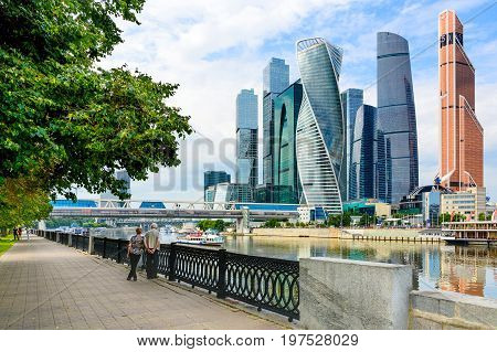 MOSCOW, RUSSIA - JULY 30: 2017:Moscow City - high modern futuristic skyscrapers of Moscow International Business Center. People walk along the embankment of the Moscow river