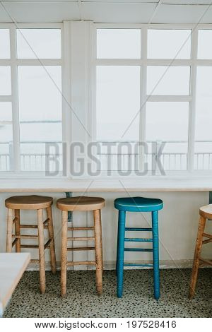 The empty cafe with wooden chairs by the window