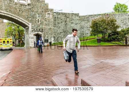 Quebec City Canada - May 31 2017: Saint John's Gate Fortress entrance to old town street with young man running in pouring rain