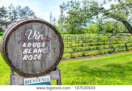 Ile D'Orleans Canada - June 1 2017: Wine barrel sign in French countryside with welcome sign by road