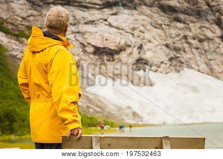 Travel concept. Tourist man looking up at rocky snowy mountains landscape in Norway
