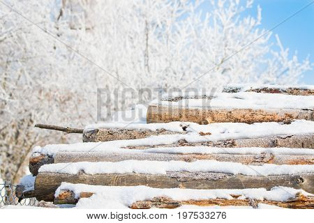 Piled up wood in winter covered in snow
