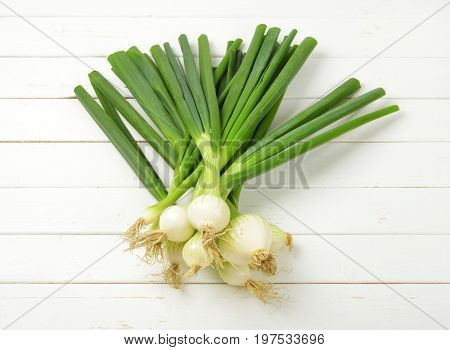 bunch of spring onion on white wooden background