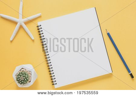 Office Workplace Minimal Concept. Blank Notebook With Starfishes, Cactus And Pencil On Yellow Backgr