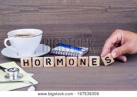 hormones. Wooden letters on dark background. Office desk
