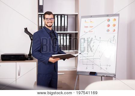 Young smiling businessman with a folder with charts in hands next to a flip-chart. Image of corporate worker analyzing financial data