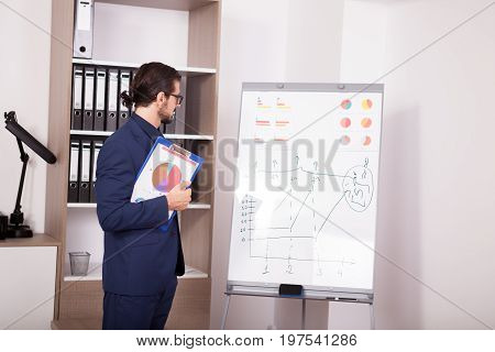 Businessman with a folder with charts in hands next to a flip-chart. Image of corporate worker analyzing financial data