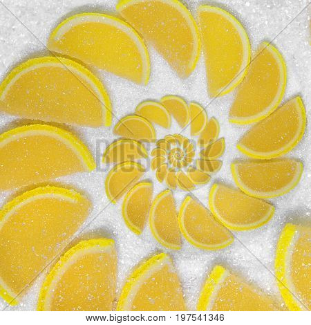 Abstract fruit jelly wedges yellow cantle lobule on white sugar background. Yellow jellies. Sweet fruit segments. Juicy fruit jelly on sugar sand Abstract food fractal Exotic sweets pattern background