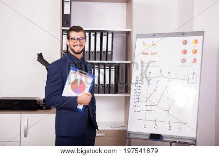 Happy businessman with a folder with charts in hands next to a flip-chart. Image of corporate worker analyzing financial data
