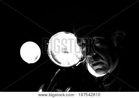 High contrast grainy image of male biker back lit by headlights staring at viewer.
