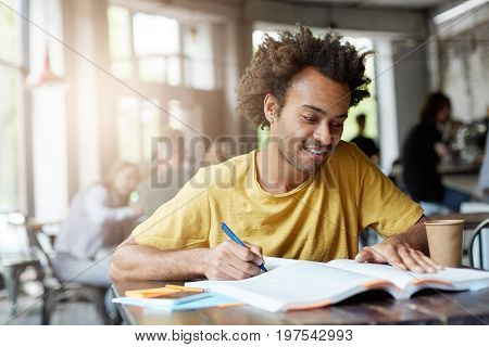 Young Dark-skinned Male Having Gentle Smile While Sitting At Table In Cozy Cafeteria Rewriting Infor