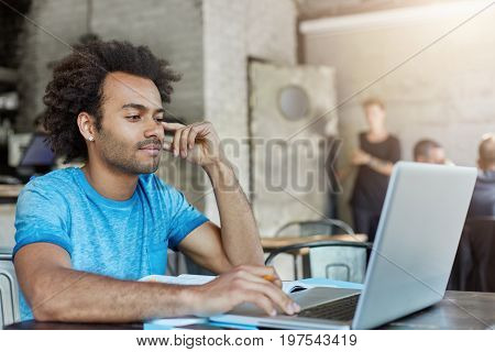 Young Black College Student With Bushy Hair And Bristle Looking Attentively At Laptop Computer Readi