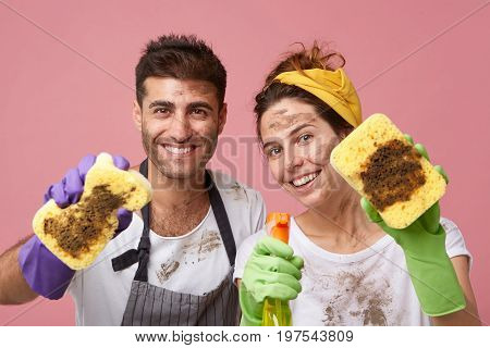 Studio Portrait Of Glad Family Couple Cleaning Everything In Their Appartment Demonstrating Dirty Sp