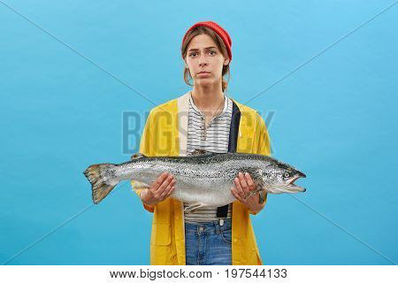Serious Female Wearing Red Hat On Head, Overalls And Yellow Raincoat Holding Huge Salmon In Hands Be