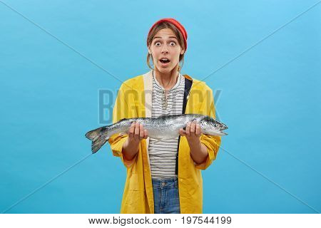 Astonished Female Angler Wearing Casual Clothes Holding Huge Salmon Looking At Camera With Widely Op