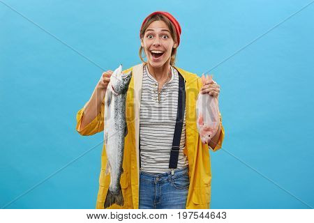 Joyful Female Angler Coming From Her Successful Fishing Trip Showing Her Catch At Camera With Very H