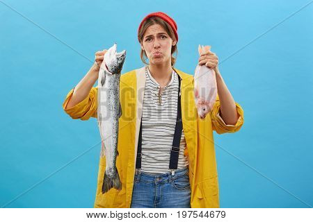 Beautiful Female Wearing Red Hat, Jean Overalls And Yellow Raincoat Having Terrible Look Being Dissa