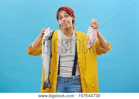 Young Doubtful Female Coming From Fishing Trip Holding In Hands Two Fish Having Hesitations Which To