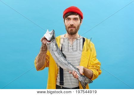Studio Shot Of Serious Confident Fisherman Coming Home After Night Fishing Holding In Hands Huge Sal