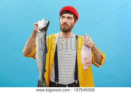 What Huge Fish! Attractive Bearded Male Having Fishing As Hobby Holding In Hands His Landing Looking