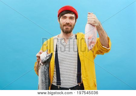 Bearded Young Man Having Good Mood After Catching Two Fish At Sea, Demonstrating His Landing At Came