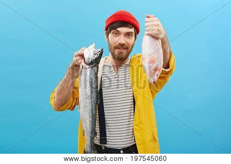 Young Caucasian Male With Blue Eyes And Dark Thick Beard Wearing Casual Clothes Holding Two Fish At